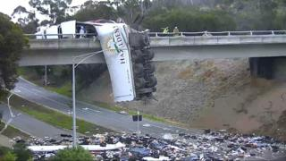 Australian truck dangles off road bridge